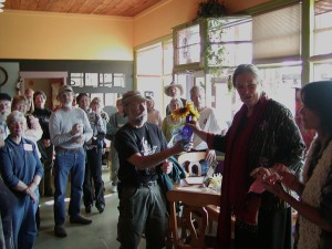 Robert Bissett accepts congratulations from Outskirts Gallery owner Kally Thurman and judge Romey Stuckart for his best of show painting created for the Third Annual Friends of Scotchman Peaks Wilderness Plein Air Paint Out.