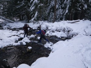 Volunteers make a stream crossing while visiting their station.